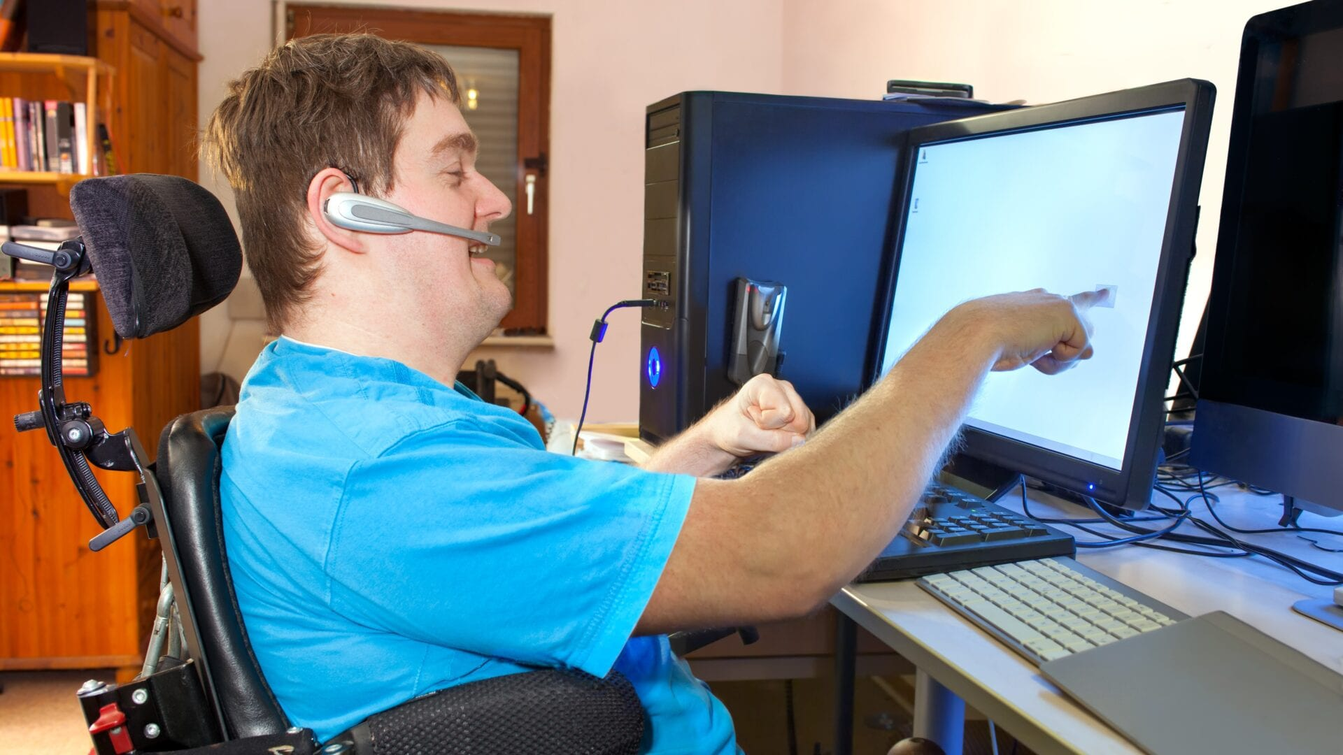 Man in a wheelchair pointing to his computer screen